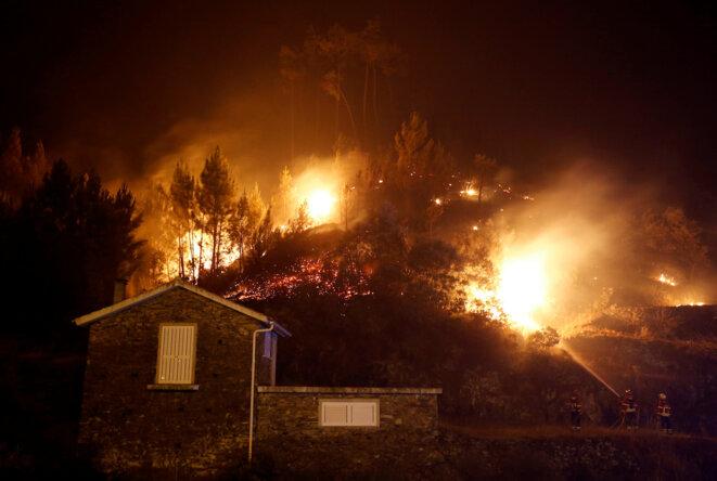 Des pompiers tentent de protéger une maison près de Carvalho (Portugal), lundi 19 juin. © Reuters