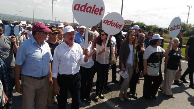 Kemal Kiliçdaroglu et les marcheurs portent des pancartes « Justice ». © N.C.