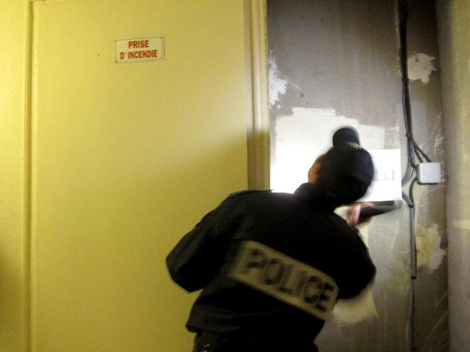 Un policier fouille des parties communes à Marseille, en 2013 © LF