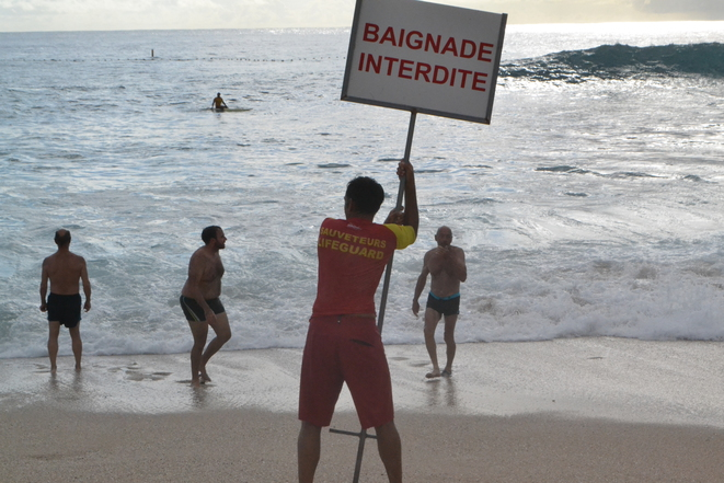 """A lifeguard holds a sign announcing """"Bathing forbidden"""". Only secured beaches are officially open to bathers on La Réunion's west coast. © Julien Sartre"""