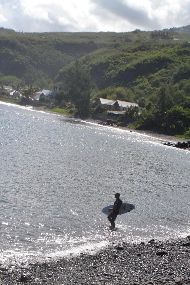 A man wades out to surf at a prohibited spot at Saint-Leu, on the west coast of La Réunion. © Julien Sartre