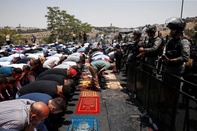 Des Palestiniens priant dans une rue près d'un barrage routier à l'extérieur de la vieille ville de Jérusalem, ce 21 juillet 2017. © REUTERS/Ronen Zvulun