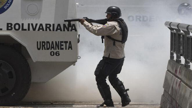 Un miembro de la Policía Nacional Bolivariana apuntando con su arma en Caracas. © DR