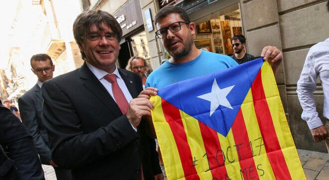 Carles Puigdemont (à gauche), le 9 juin 2017 à Barcelone, avec un drapeau de la Catalogne à la main © Albert Gea / Reuters.