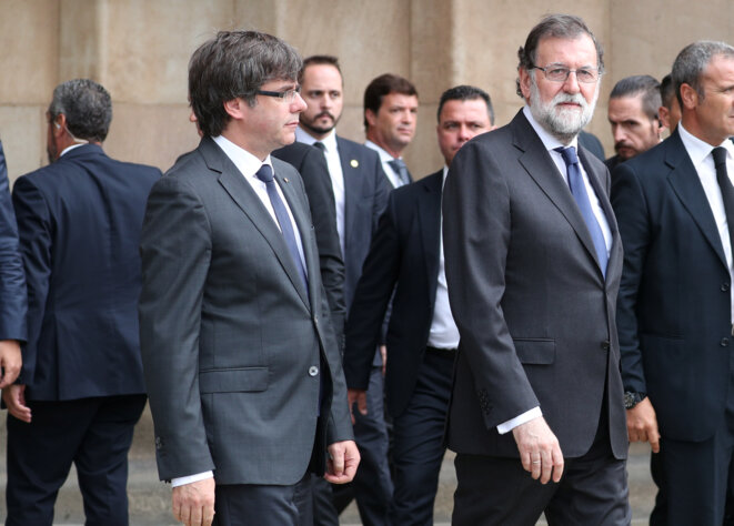 Moment rare dans la politique espagnole : Carles Puigdemont, président de la Generalitat à Barcelone, et Mariano Rajoy, chef du gouvernement à Madrid, côte à côte, à la sortie d'une messe en mémoire des victimes des attentats, le 20 août 2017, à Barcelone © Sergio Perez / Reuters