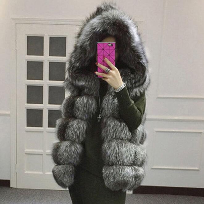 Cachée derrière son smartphone - un manequin porte une veste en fourure de renard argenté