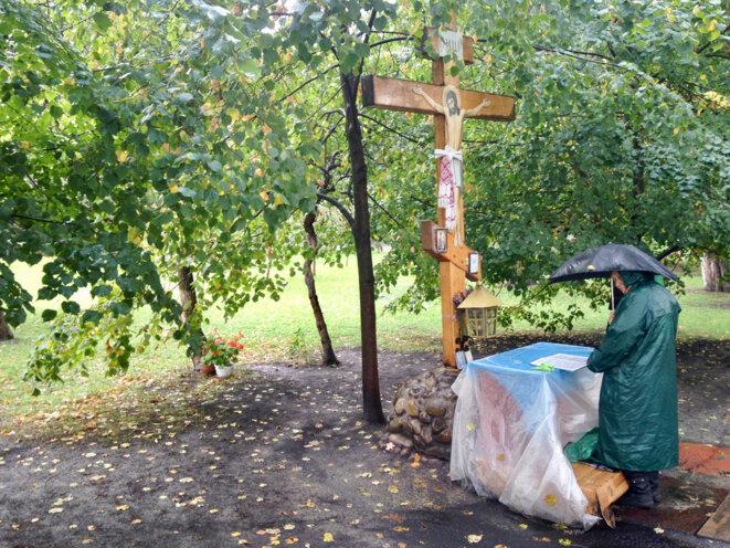 Une vieille dame prie dans un parc juste en face de l'entrée du Parlement ukrainien.