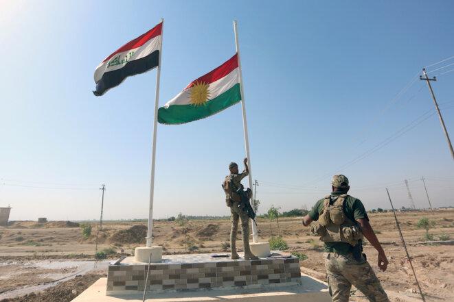 Un soldat des forces irakiennes descend le drapeau kurde à Kirkouk, le 16 octobre 2017 © Reuters