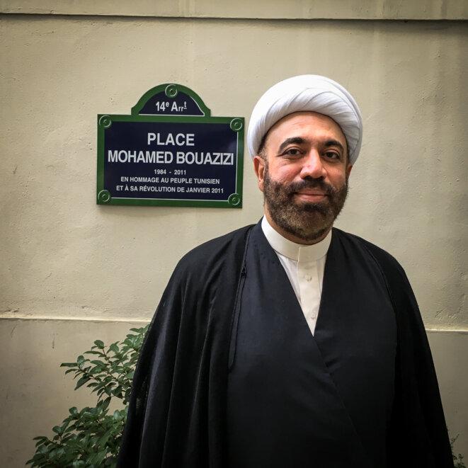 Le cheikh Maytham al-Salman posant devant une plaque en hommage au jeune Tunisien qui a involontairement déclenché les printemps arabes de 2011, dans les locaux de la FIDH à Paris © Thomas Cantaloube
