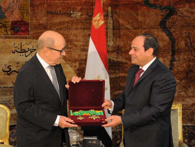 Jean-Yves Le Drian recevant des mains d'Abdelfattah al-Sissi des médailles pour le récompenser de la coopération militaire entre la France et l'Égypte, en février 2017. © Reuters