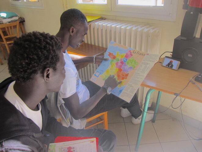À la salle paroissiale de Gap, ces deux jeunes calculent la distance pour se rendre à Saint-Étienne, où ils espèrent pouvoir étudier © LF