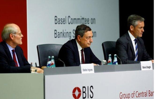 Le président de la BCE, Mario Draghi, entouré de Stefan Ingves et de William Coen, respectivement président et secrétaire général du Comité de Bâle, le 7 décembre. © Reuters