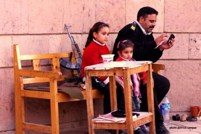 Policier Egyptien devant une église Copte accompagné de ses filles © Patrick Compas