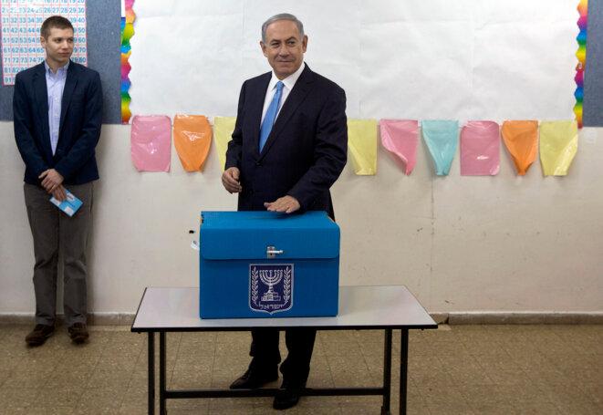 Yaïr Netanyahou accompagne son père au bureau de vote, en 2015. © Reuters