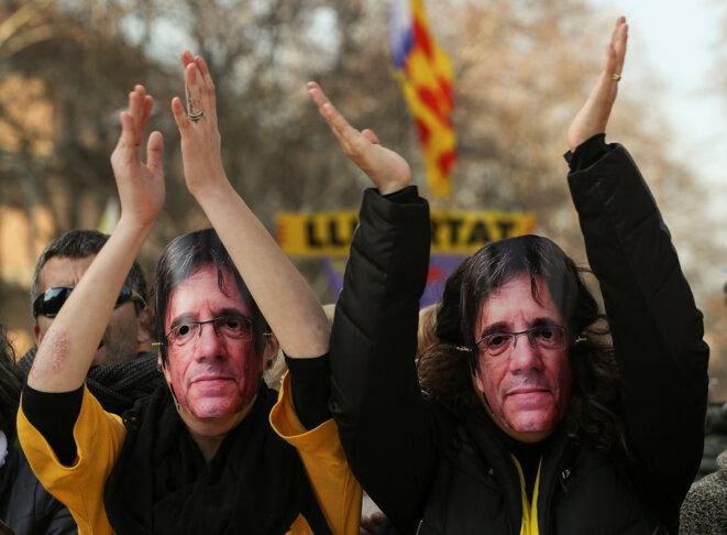 À l'extérieur du parlement catalan, mardi 30 janvier, des indépendantistes portent un masque de Puigdemont. Ils cherchent à brouiller les pistes des forces de l'ordre, pour aider Puigdemont à revenir incognito à Barcelone, afin d'être investi. © Reuters / Sergio Perez.