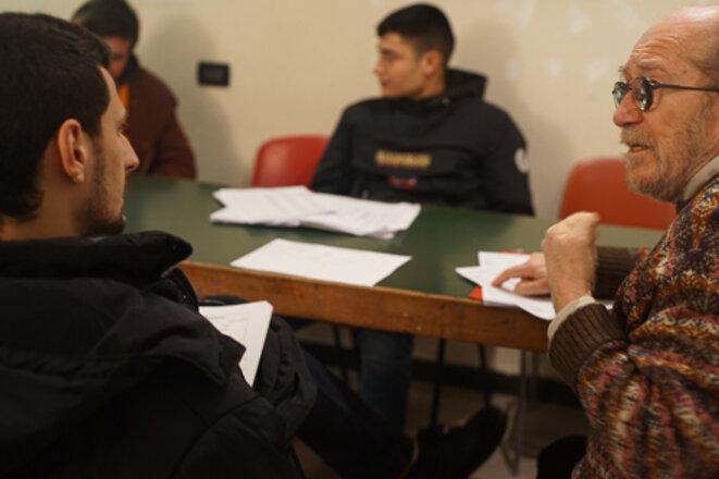 Giuliano Giuliani donne un cours d'italien à des exilés © Amélie Poinssot