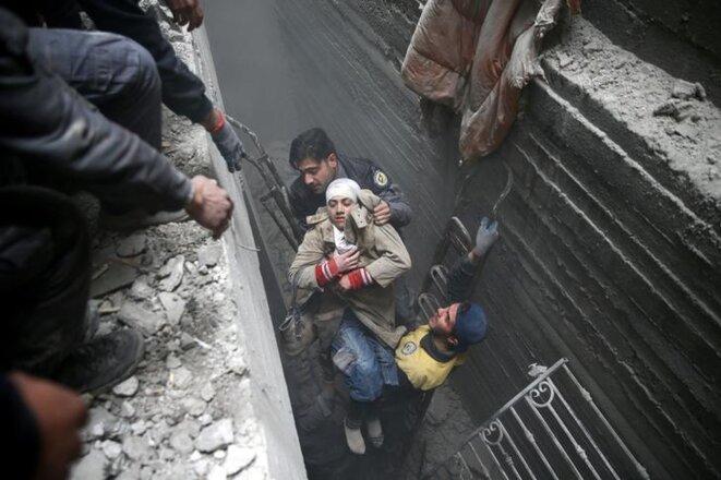 Des équipes de secours de la Défense civile syrienne extraient une femme des décombres de sa maison, à Douma, ville assiégée de l'est de la Ghouta. © Reuters