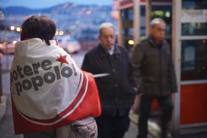Distribution de tracts d'une militante de Potere al Popolo!, à Gênes en février 2018. © Amélie Poinssot.