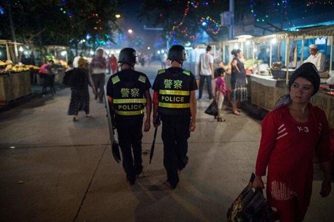 La police chinoise patrouille le marché nocturne près de la mosquée Id Kah à Kashgar, dans la région autonome ouïghoure du Xinjiang en Chine, un jour avant les vacances de l'Aïd al-Fitr, le 25 juin 2017. © AFP PHOTO / Getty Images