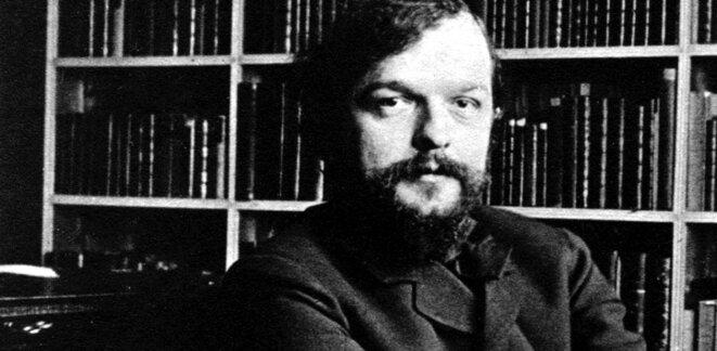 Claude Debussy, devant la bibliothèque du compositeur Paul Dukas.