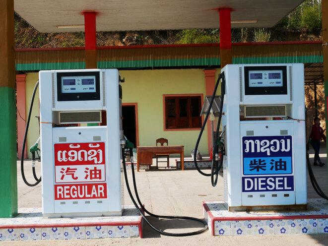 Tout au long de la route, les panneaux dans les stations-essence ou sur les terrains à vendre sont en trois langues, laotien, anglais, chinois, et parfois aussi en vietnamien et coréen. © Laure Siegel