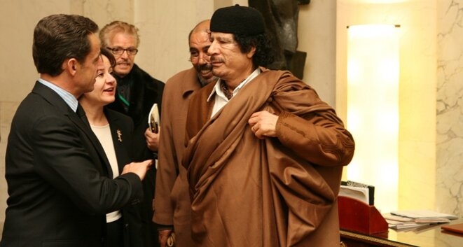 Nicolas Sarkozy et Mouammar Kadhafi avec leurs interprètes. À l'arrière de Kadhafi, Moftah Missouri. © DR