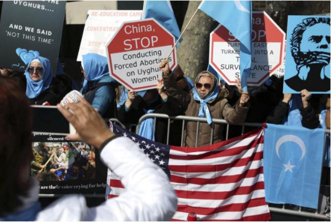 Les Ouïghours et leurs soutiens se rassemblent de l'autre côté de la rue du siège des Nations Unies à New York le 15 mars. © Seth Wenig/AP