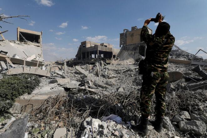 Un soldat syrien filme les ruines du Centre d'études et de recherches scientifiques, à Barzeh, dans l'agglomération de Damas. © REUTERS/Omar Sanadiki