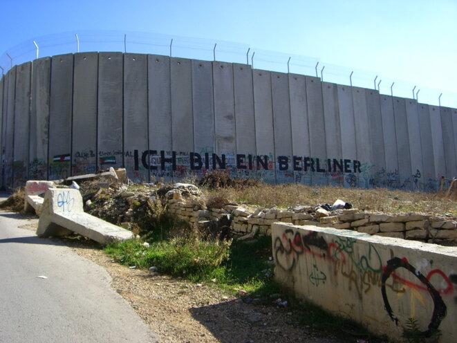 """Le mur de séparation israélien en Cisjordanie, en direction de Béthleem, décembre  2007. Graffiti reprenant la phrase célèbre de John F. Kennedy lors de sa visite à Berlin-Ouest le 26 juin 1963: """"Ich bin ein Berliner!"""" (trad.: """"Je suis un Berlinois!""""). Source: Wikimedia Commons. © Marc Venezia."""