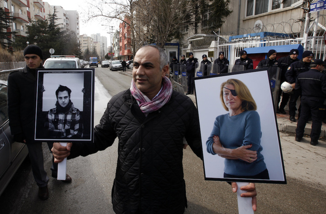 Un manifestante en Turquía sostiene los retratos de Rémi Ochlik y Marie Colvin en febrero de 2012 para denunciar el asesinato de periodistas por el régimen de al-Assad. © Reuters