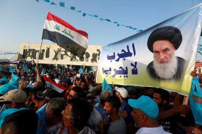 Bagdad, vendredi 4 mai. Des militants chiites arborent un poster de l'ayatollah Ali al-Sistani. © REUTERS/Alaa al-Marjani