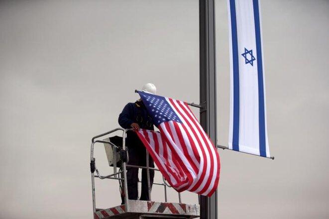 Un ouvrier accroche un drapeau américain à côté d'un drapeau israélien, à l'entrée du consulat des États-Unis à Jérusalem, le 7 mai 2018. © REUTERS/Ronen Zvulun