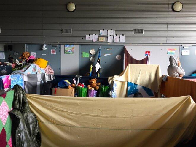 À l'intérieur du gymnase, les familles se sont recréé des espaces individuels en délimitant des espaces avec des lits picot et des draps tendus. © EP