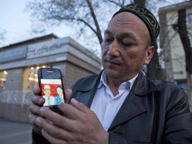 Omir Bekali montre une photo de ses parents qui, selon lui, ont été internés en Chine © AP