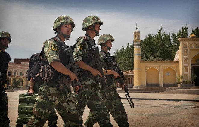 Les soldats chinois défilent devant la Mosquée Id Kah, la plus grande de Chine, le 31 juillet 2014 à Kashgar, en Chine. © Getty Images
