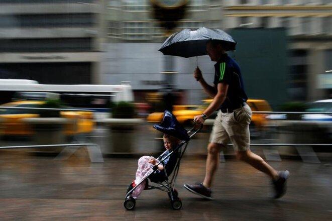 Un homme court sous la pluie avec son enfant à Manhattan, août 2016. © Eduardo Munoz/Reuters