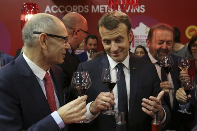 Sharing a glass: Emmanuel Macron at the Salon de l'Agriculture farming show in 2018. © Reuters