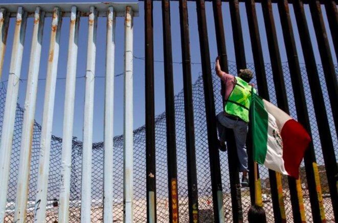À Tijuana (Mexique), un manifestant grimpe sur la barrière construite sur une partie de la frontière entre les deux pays pour protester contre la politique migratoire de Donald Trump. © Reuters