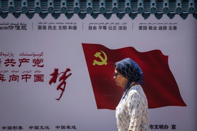 Une femme ouïghoure passe devant le drapeau du Parti communiste chinois sur un mur à Urumqi, dans la région autonome ouïghoure du Xinjiang, le 27 juin 2017 © Getty Images