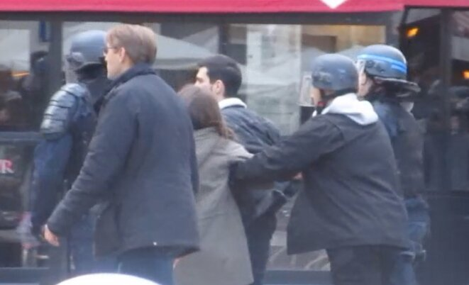 This still from the video by Renaud Delacroix shows Alexandre Benalla (with white hood, second from right) leading the young couple he assaulted and then had arrested towards another spot on the Contrescarpe square. He is accompanied by two CRS officers and plainclothes police officer, Philippe Mizerski. © DR