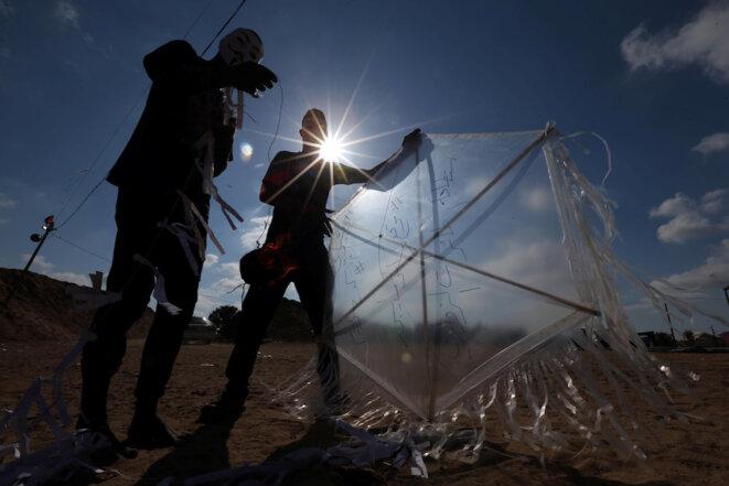 Des Gazaouis se préparent à lancer un cerf-volant enflammé en direction d'Israël © Reuters
