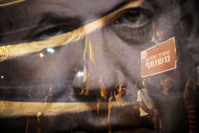 Un poster de Netayahou se reflète dans une vitrine lors d'une manifestation contre la loi sur l'État-nation juif. La pancarte dit: «Le futur de nos enfants est en commun» © Reuters