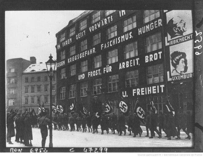 """Manifestation nazie de janvier 1933 devant le siège du KPD (Parti communiste allemand). Sur l'immeuble, on lit """"In ihrem geist Vorwärts im kampf"""" soit """"Dans son esprit, en avant dans la lutte""""; puis """"Gegen kriegsgefahr faschismus hunger und frost, für arbeit, brot u. freiheit """" soit """"Contre le danger de la guerre, du fascisme, de la faim et du gel, pour le travail, le pain et la liberté"""". © Photo de presse de Robert Sennecke Internationaler Illustrations Verlag (agence photographique) et diffusée par l'Agence Mondial, Paris, janvier 1933,"""