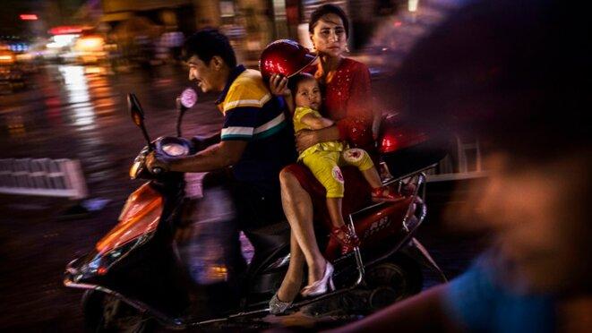 Une famille ouïghoure monte sur un scooter à Kashgar, dans le Xinjiang, en Chine, en 2017 © Kevin Frayer/Getty
