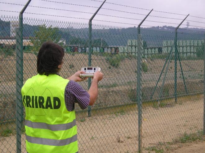 La CRIIRAD mesure le niveau de radiation dans le domaine accessible au public devant le parc à fûts de l'usine de Malvesi © CRIIRAD 2006