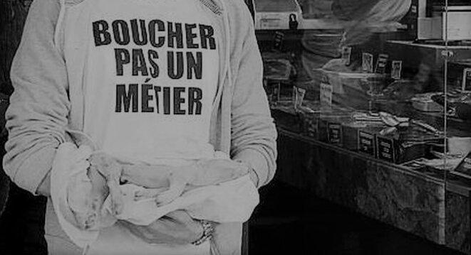 Un militant du collectif Boucherie Abolition devant une vitrine de boucherie samedi 22 septembre - ©Agence France Presse © Agence France Presse