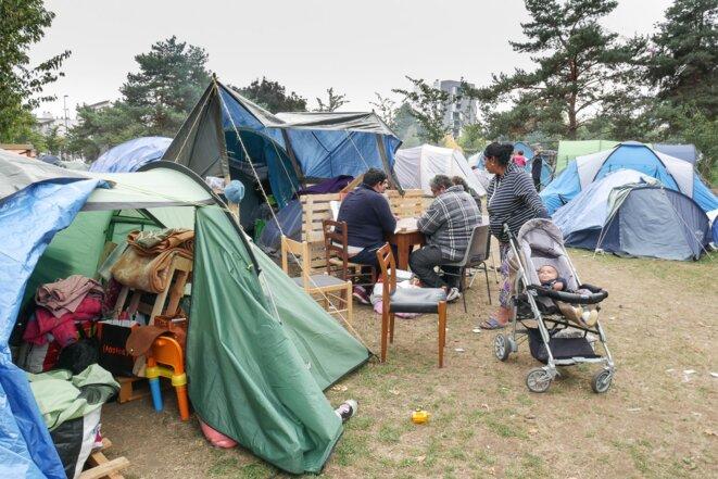 A l'étroit sous les tentes, des hommes jouent aux cartes tandis que le bébé attend dans la poussette © Georges