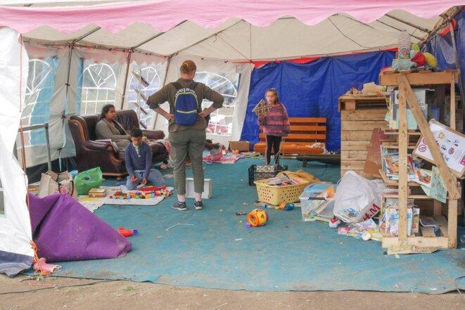 Sous un barnum aménagé grâce aux dons de livres et jeux, un espace pour les enfants sous le regard des mères et bénévoles © Georges