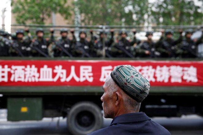 Un homme ouïghour face à des militaires chinois au Xinjiang, le 23 mai 2014. © Reuters