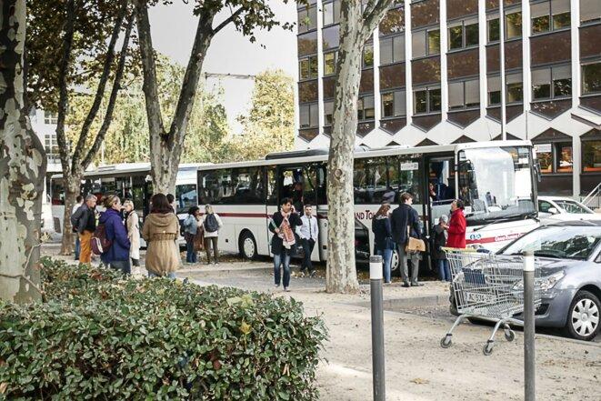 Des migrants montent dans le bus sous l'oeil de bénévoles et de fonctionnaires préfectoraux © Georges